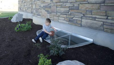 little boy sitting on plastic basement window well cover